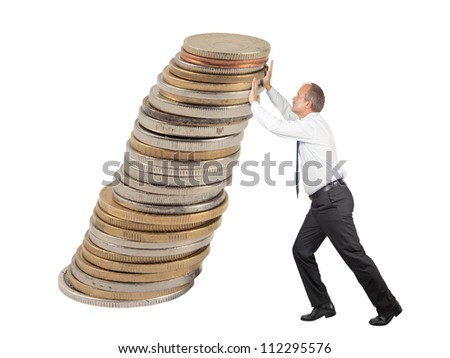 Business man pushing some coins upwards to avoid them from falling down - stock photo