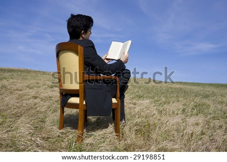 Business man reading a book on the meadow - stock photo