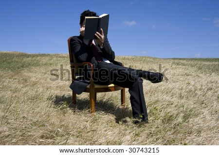 Business man reading a book on the meadow