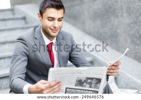 Business man reading a newspaper sitting on the stairs  - stock photo