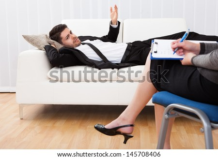 Business man reclining comfortably on a couch talking to his psychiatrist explaining something - stock photo
