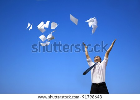business man relaxing and throwing white papers  to the blue sky - stock photo