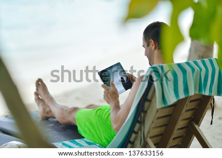 business man relaxing and use tablet computer at beautiful tropical beach - stock photo