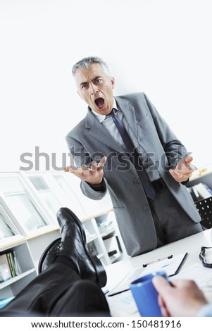Business man relaxing at desk while his boss shouting angry - stock photo