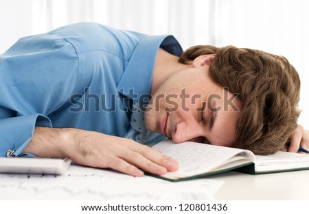 Business man resting head on notebook - stock photo