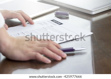 Business man review his resume on his desk, resume information with hand, pen, digital tablet, computer laptop.