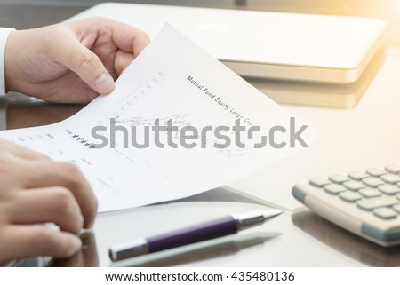 Business man review Mutual Fund information with performance graph, pen calculator and laptop computer. Warm tone - stock photo