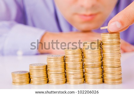 Business man rising coins - stock photo