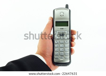 Business man's hand holding a cordless phone isolated on white - stock photo