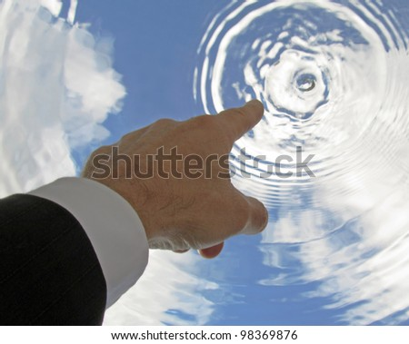 Business man's hand pointing to sky causing sky to ripple