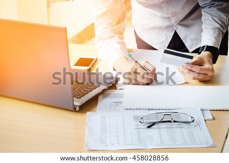 Business man's hands holding a credit card Writing payment document and using laptop for online shopping vintage tone - stock photo