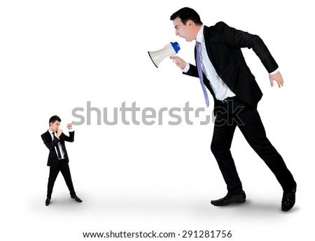 Business man screaming on megaphone on little man - stock photo