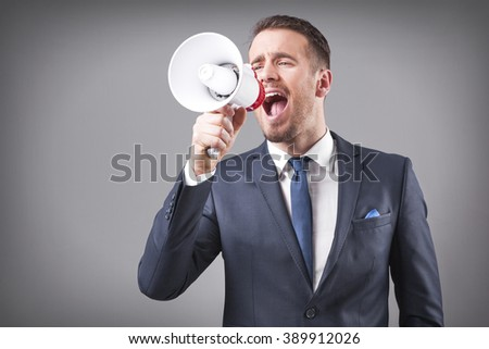 Business man screaming with a megaphone on grey background - stock photo