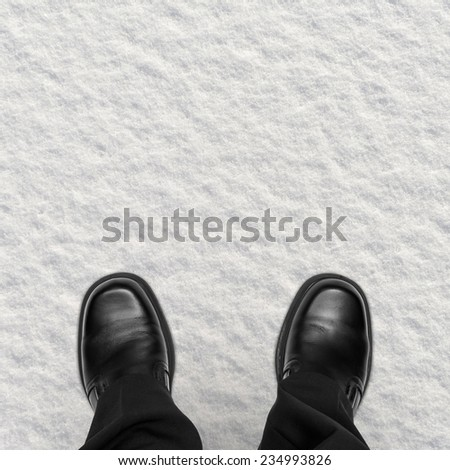 Business man shoes in snow, overhead view - stock photo