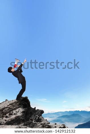 business man shouting into a megaphone and finger point to copy space on a mountain, asian model - stock photo