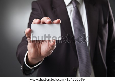 business man show card on dark grey background - stock photo