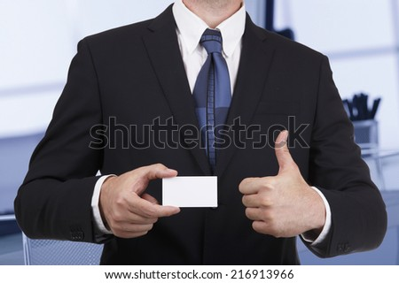 Business man showing a blank card gesturing thumbs up - stock photo