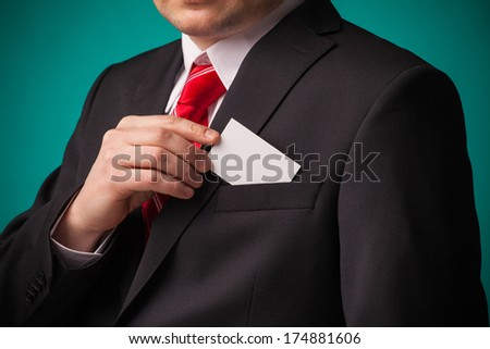 Business man showing a blank empty business card over green background  - stock photo