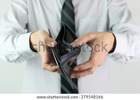 Business man showing an empty wallet for no money concept - stock photo