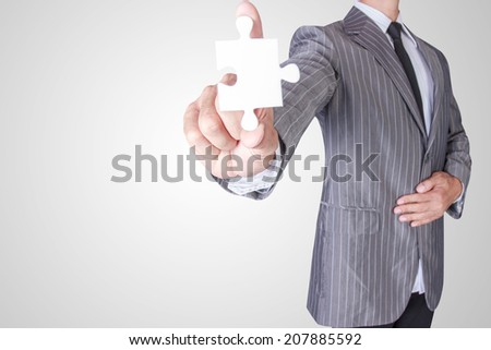 business man showing blank jigsaw puzzle piece with concept for business  success  - stock photo