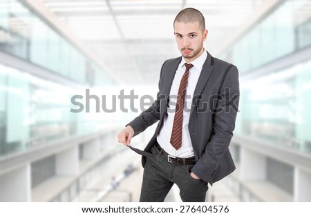 business man showing his empty pocket, at the office - stock photo