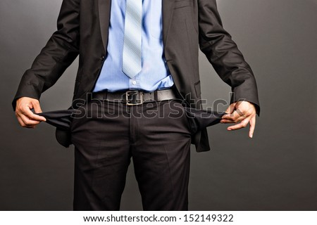 Business man showing his empty pockets  on gray background - stock photo