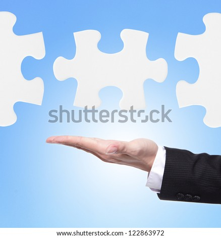 Business man showing jigsaw puzzle piece in the air with blue background, Concept for business strength and success.
