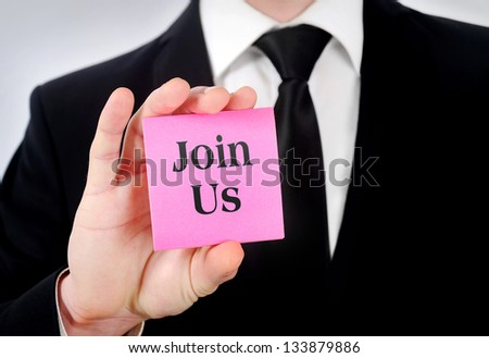 Business man showing postcard on camera - stock photo