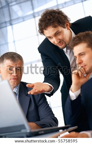 Business man showing something on laptop to his colleagues.