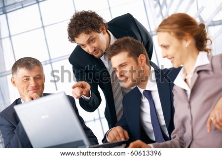 Business man showing something on laptop to his colleagues. - stock photo