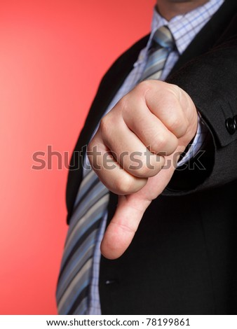 Business man showing thumb down - selective focus on hand - stock photo