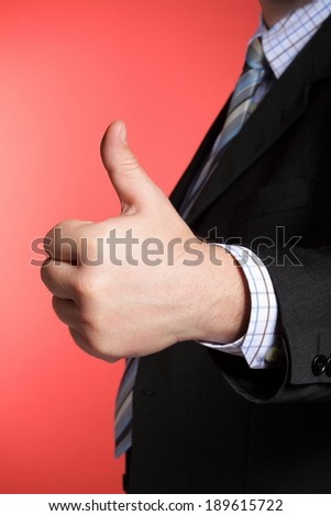 Business man showing thumb up - selective focus on hand - stock photo