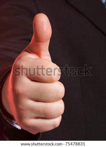Business man showing thumb up - selective focus on hand