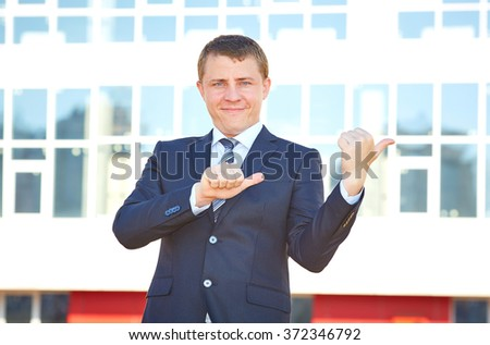 Business man shows a finger to the side. Lots of copy space for advertising text. Pointing to. Modern business man in suit and tie.