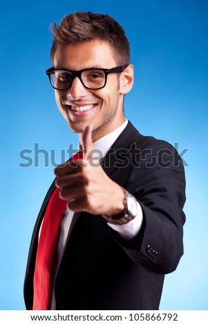 Business man shows thumbs up ok gesture on blue background - stock photo