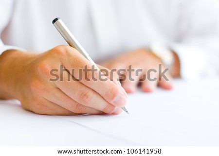 Business man signing the contract - shallow focus on signature
