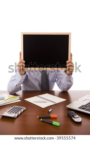Business man sit at his desk holding a blank blackboard