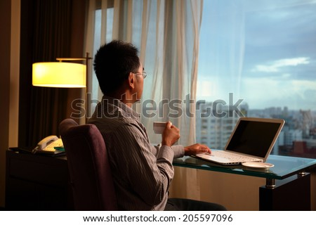 business man sit in a room and looking into the distance in hotel, concept of traveling business, dream, work at night etc. asian - stock photo
