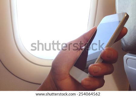 business man sits in airplane watching his cell phone - stock photo