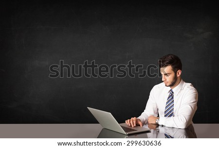 Business man sitting at black table with a laptop on black background - stock photo