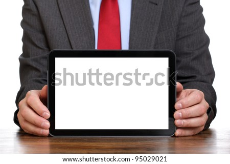 Business man sitting at desk holding digital tablet displaying a white screen for copy - stock photo
