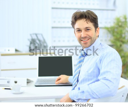 Business man sitting at his desk in the office with a laptop - stock photo