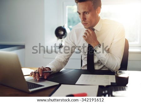 Business man sitting at his desk working on a computer and looking concentrated - stock photo