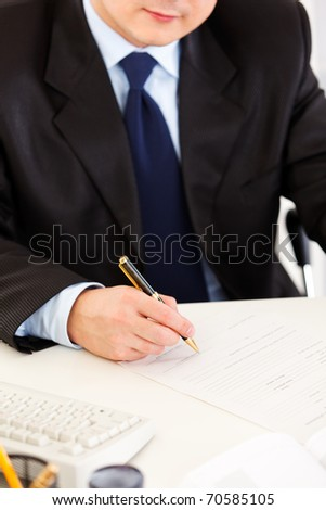 Business man sitting at office desk and signing document. Close -up.