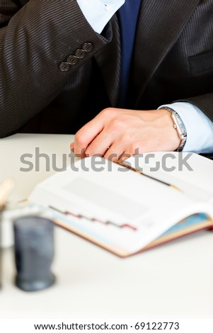 Business man sitting at office desk with diary.  Close-up on hands.