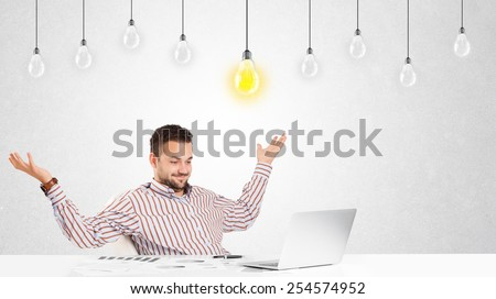 Business man sitting at table with bright idea light bulbs - stock photo