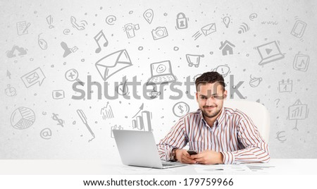 Business man sitting at table with hand drawn media icons and symbols - stock photo