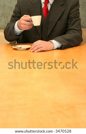 Business-man sitting at the desk, drinking coffee or tea. - stock photo