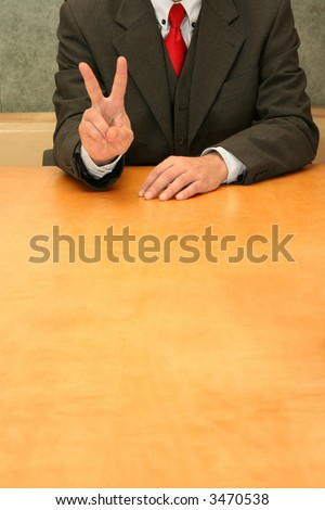 Business-man sitting at the desk, indicating number two or victory. - stock photo
