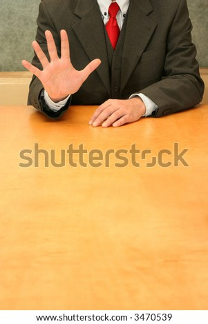 """Business-man sitting at the desk making a """"five"""" or """"wait"""". - stock photo"""